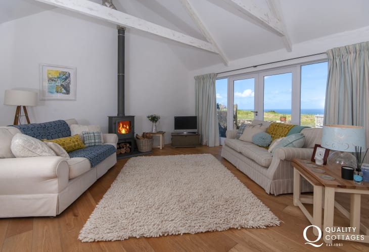 Abereiddy, Pembrokeshire restored holiday cottage - spacious living room with log burning stove and doors to the patio