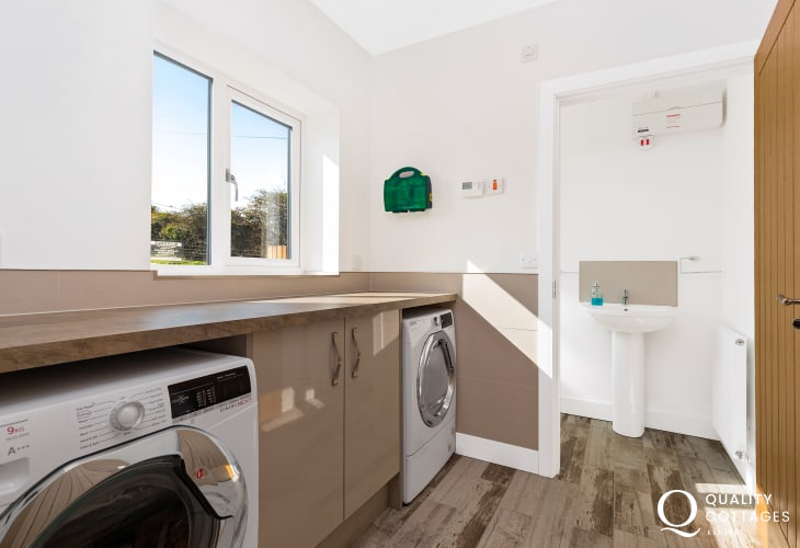 Contemporary ulitlity room with washing machine and tumble dryerleading to cloakroom