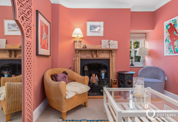 Snug seating area with coffee table, large mirror, fireplace and lamps in large holiday cottage on the St Davids Peninsula.