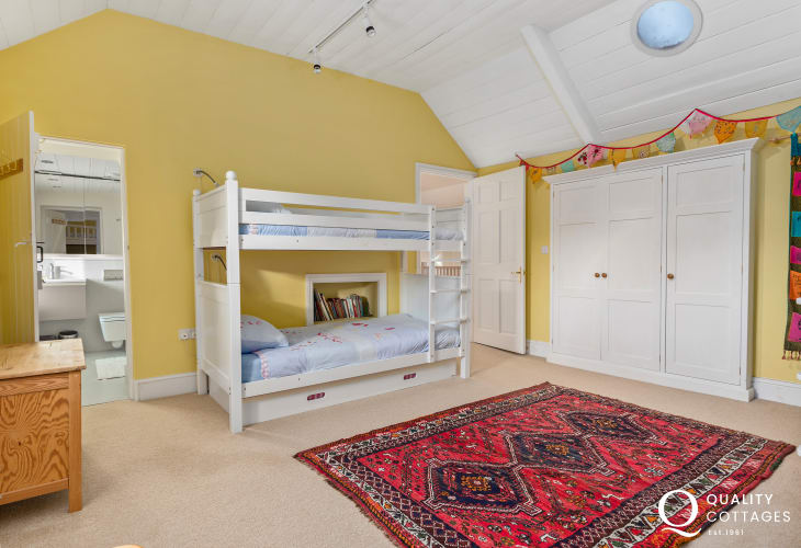 Holiday cottage in Pembrokeshire - Children's bedroom with ensuite, sleeping five, with toy cupboard and dressing up box.