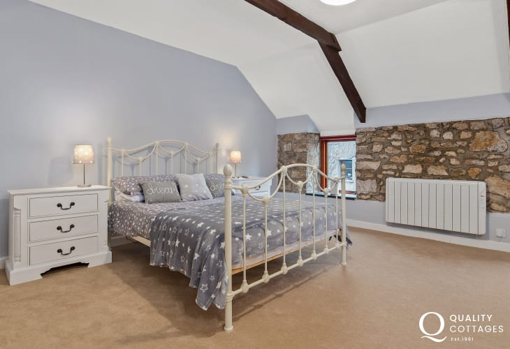 Kingsize bed in the spacious master bedroom at Owl's Retreat holiday cottage in Pembrokeshire.