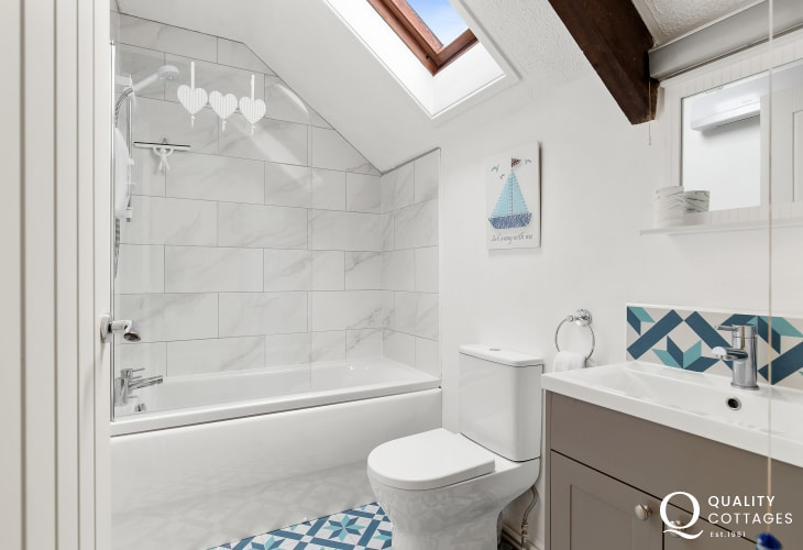 Clean and bright bathroom in Owl's Retreat holiday cottage - shower over bath.