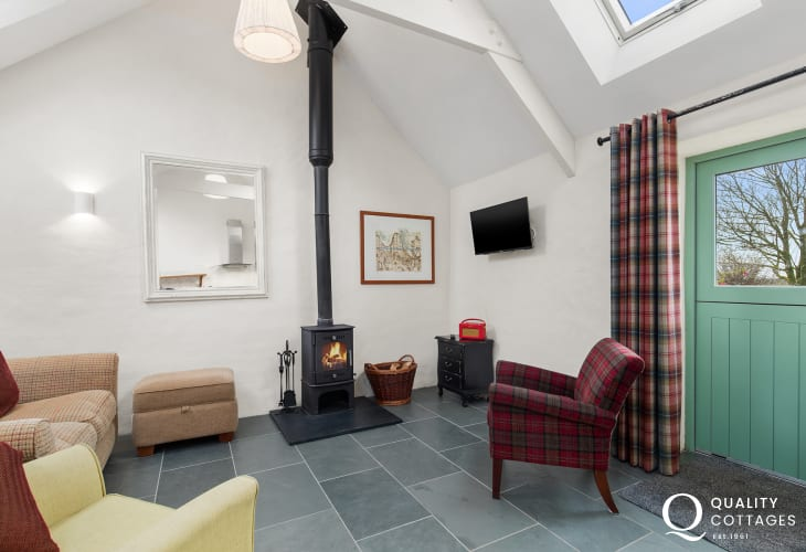 Lounge with log burner, TV, sofa and armchairs in dog friendly holiday cottage in rural Pembrokeshire, near Preseli Mountains