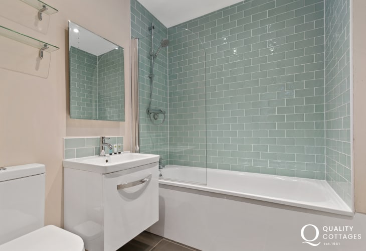 Holiday cottage in rural Rhosfach, Pembrokeshire - Family bathroom with bath, over bath shower, washbasin, mirror and WC.