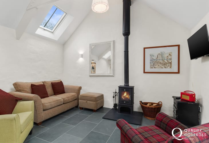 Holiday cottage by the Preseli mountains, Pembrokeshire - Cosy lounge with armchairs, sofa, footstool and wood-burning stove.