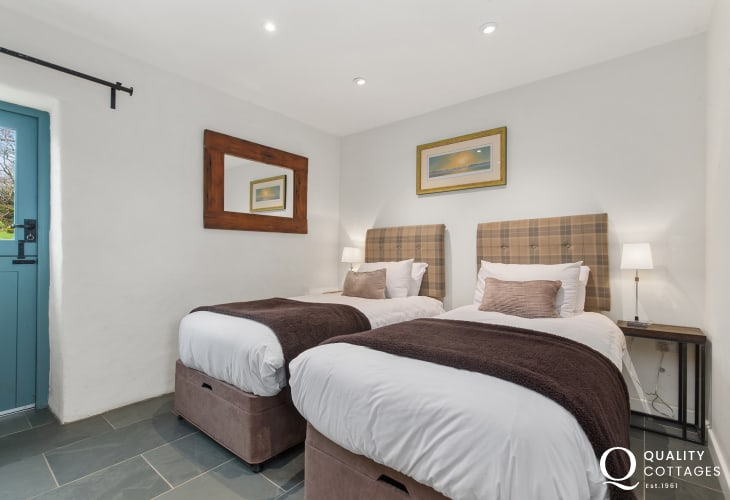 Twin bedroom with bedside tables, lamps and a stable door