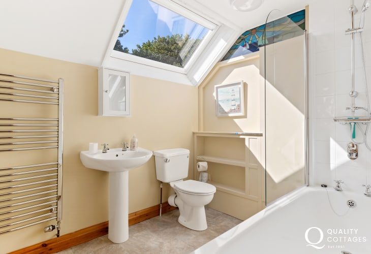 Bright family bathroom with sink, toilet and shower over bath.