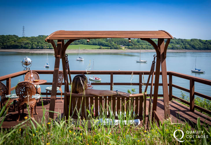 Chair swing on decking of holiday home with views over the river in Pembrokeshire