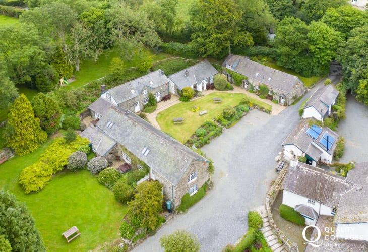 Aerial photo of the grounds of holiday cottage in Cardigan Bay with tennis court, children's play area and swimming pool.