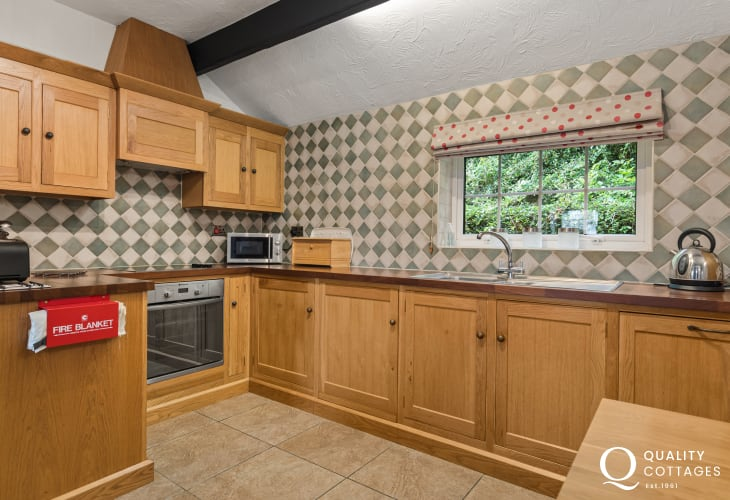 Oak kitchen with dishwasher, washing machine, fridge/freezer and microwave in holiday cottage in New Quay, Cardigan Bay.
