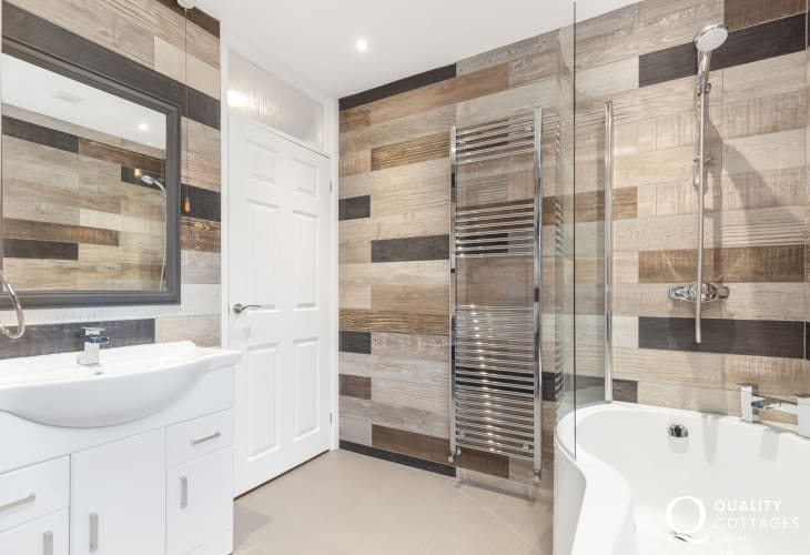 Family bathroom with bath and over shower, washbasin, WC and heated towel rail