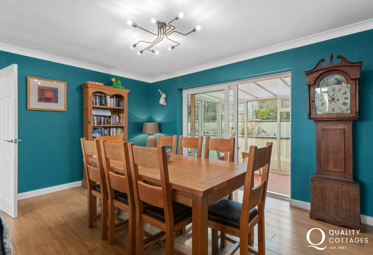Open plan dining area with large dining table and chairs in holiday cottage in Saundersfoot, Pembrokeshire.
