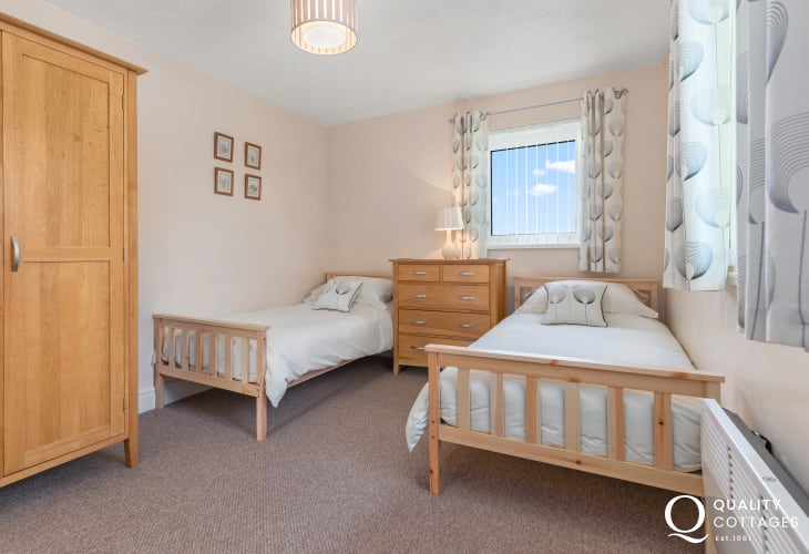 Twin bedroom with chest of drawers and wardrobe in holiday apartment with rural views over golf course in Pembrokeshire.