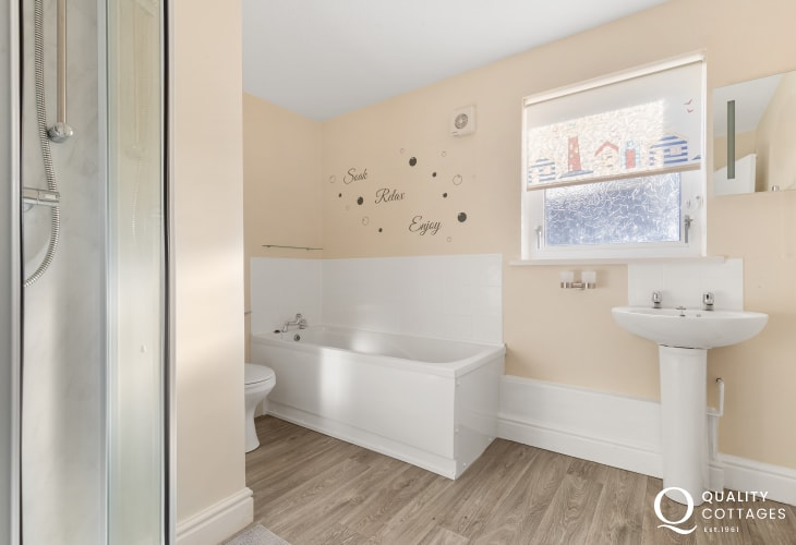 Holiday apartment on golf course in Pembrokeshire - Family bathroom with shower enclosure, washbasin, bath and WC.