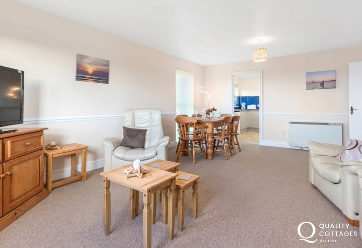 Holiday apartment on golf course in Pembrokeshire - open plan living room / dining room with TV, Sofa and armchairs.