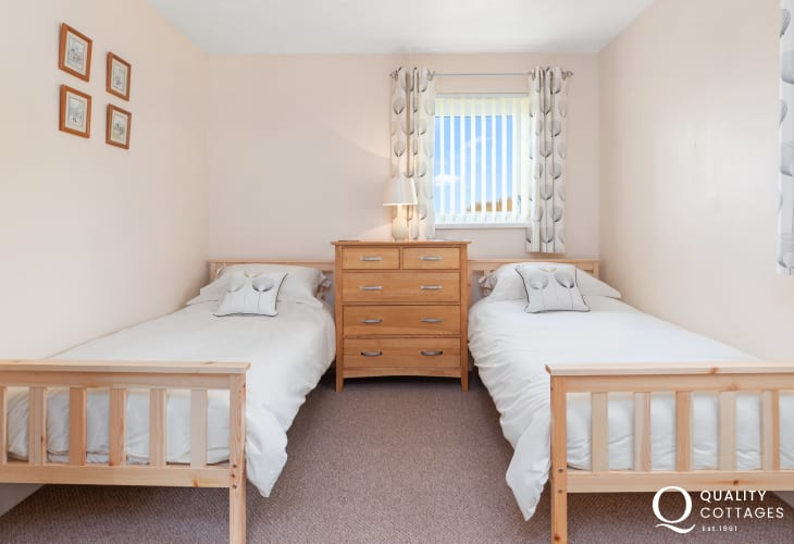 Twin bedroom with chest of drawers and rural countryside views over the golf course - holiday apartment in Pembrokeshire.