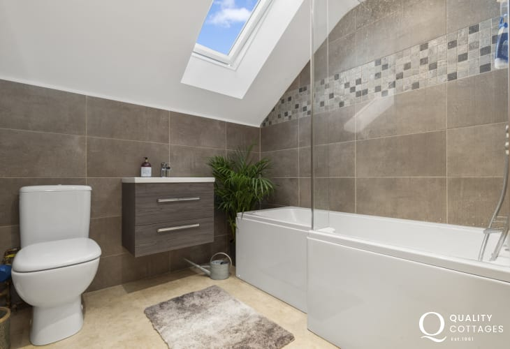 Holiday apartment in St Davids, Pembrokeshire. Modern family bathroom with bath, over shower, WC, washbasin and velux window.