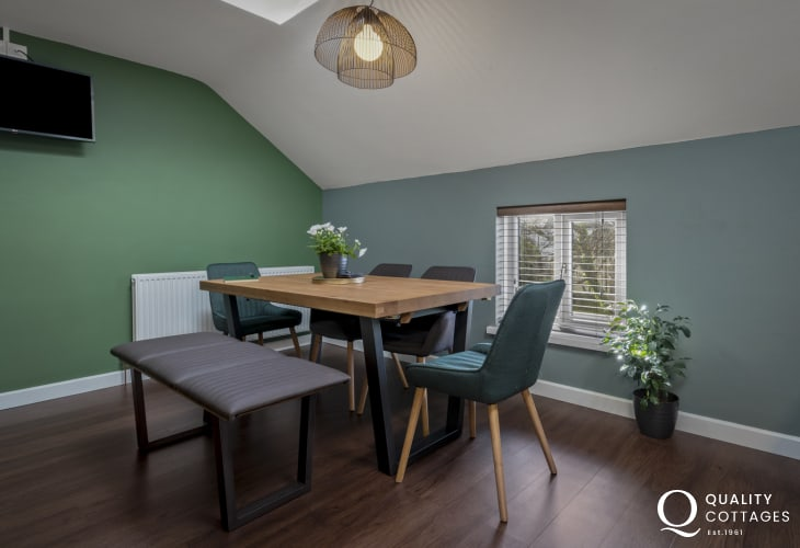 Modern dining table with seating for six inside holiday apartment in the heart of St Davids city, Pembrokeshire.
