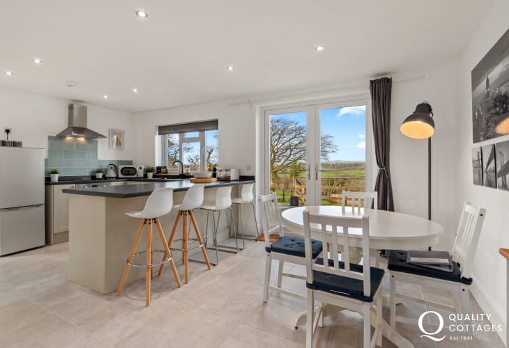 Holiday cottage Narberth, Pembrokeshire - modern open plan kitchen-diner with island and stools with countryside views.