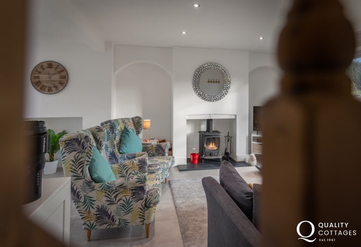 Dog friendly holiday cottage near Narberth, Pembrokeshire. View into the lounge with log-burner, armchairs and log burner.