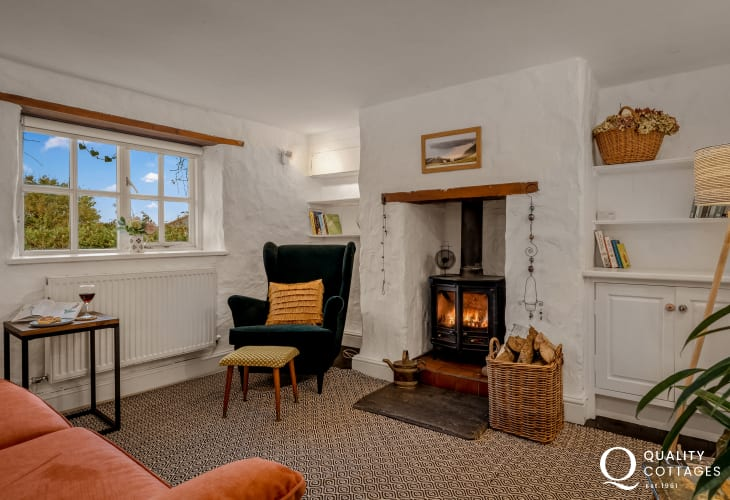Pet friendly holiday cottage in Bosherton, Pembrokeshire - lounge with log burner, wing-back chair and sofa.