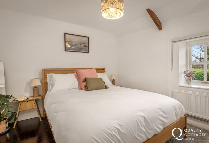 King-size bedroom with exposed beams in traditional holiday cottage in rural Bosherton, Pembrokeshire.