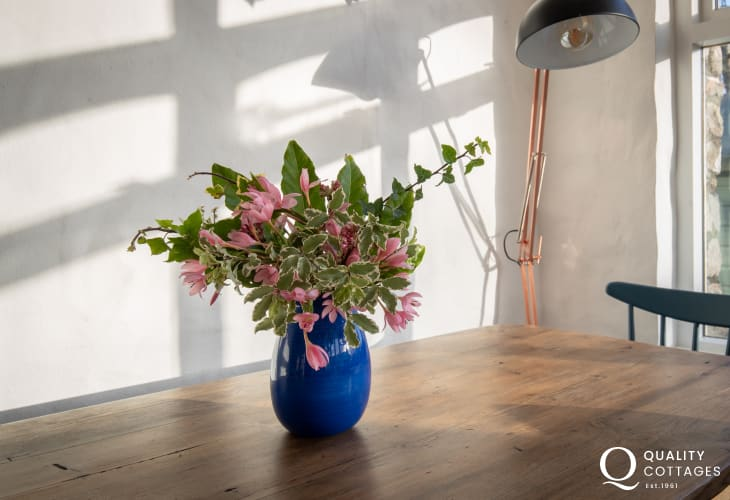 Vase of flowers on dining table of holiday cottage next to Bosherton Lily Ponds, Pembrokeshire.