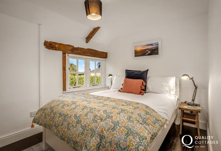 King-size bedroom with traditional exposed beams and wooden floor, next to Bosherton Lily Ponds, Pembrokeshire.
