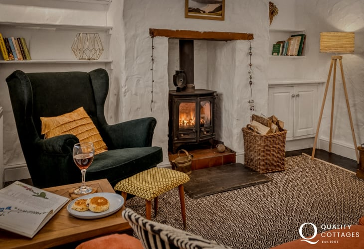 Holiday cottage in Bosherton, Pembrokeshire - Cosy lounge with log burner, wing-back chair and sofa.