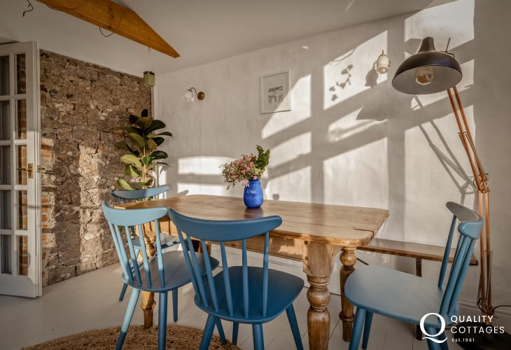 Dining area with large anglepoise lamp and wooden dining table, seating six - holiday cottage in Bosherton  Pembrokeshire.
