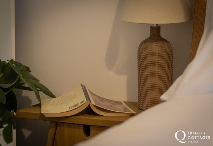 Bedside table with lamp in king size bedroom of holiday cottage in Bosherton, Pembrokeshire.