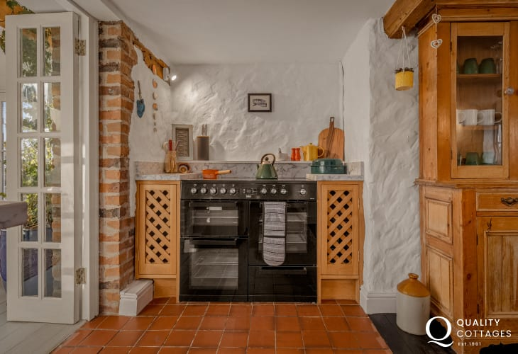 Range cooker in kitchen of traditional period holiday cottage in Bosherton, Pembrokeshire.