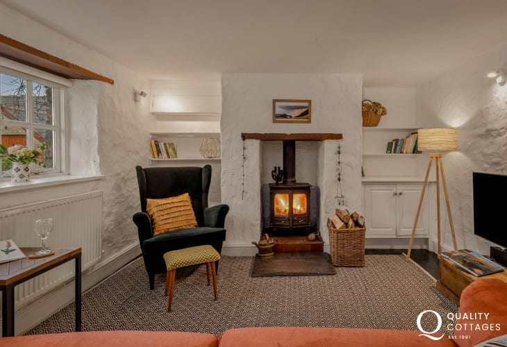 Stylish lounge with log burner, wing-back chair and sofa - dog friendly holiday cottage in Bosherton, Pembrokeshire.