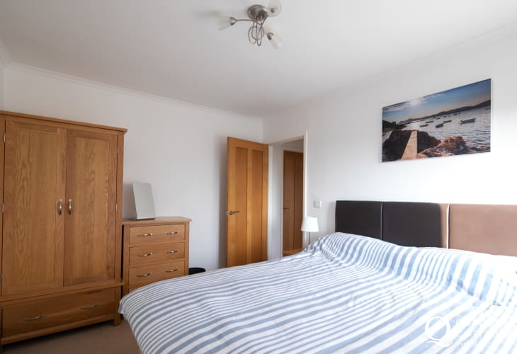Double bedroom with wardrobe, bedside table and chest of drawers - holiday cottage in Morfa Nefyn, North Wales - sleeps 8