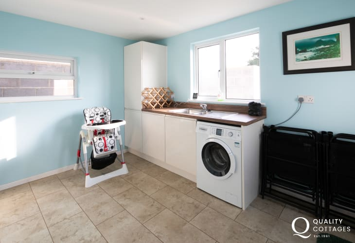 Pet friendly holiday cottage in Morfa Nefyn, North Wales - Utility room with highchair, cot, washing machine and clothesline.