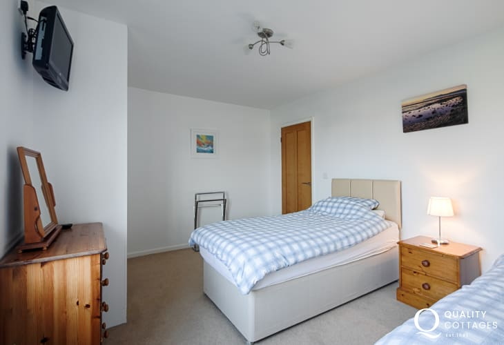 Twin bedroom with bedside table, lamp, chest of drawers and TV - coastal holiday cottage in Morfa Nefyn, North Wales