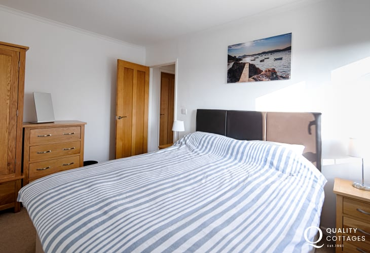 Double bedroom with oak wardrobe, chest of drawers and bedside table inside holiday cottage on Llyn Peninsula. Sleeps 8.