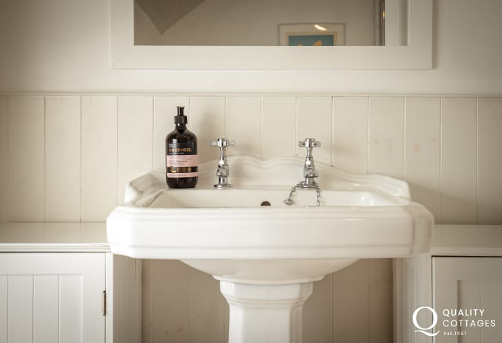Family bathroom with bath, shower, mirror, WC, heated towel rail and washbasin - holiday cottage in Solva, Pembrokeshire.
