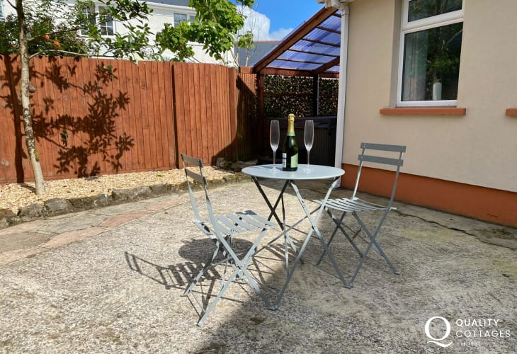 The enclosed patio garden with seating, hot tub - pet friendly holiday cottage near Amroth, Pembrokeshire - sleeps two.