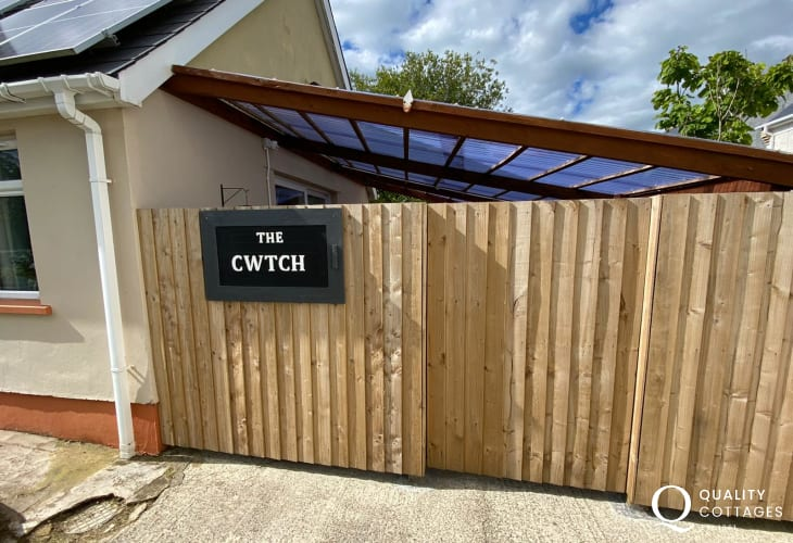 Front of Cwtch holiday cottage near Amroth, Pembrokeshire with name plaque sign.