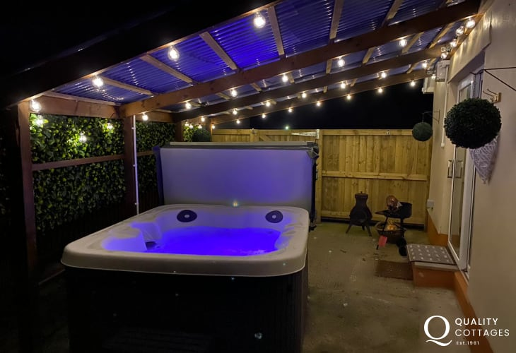 Luxury hot tub lit up at night under canopy shelter - romantic holiday cottage in Llanteg, Pembrokeshire, sleeping two.