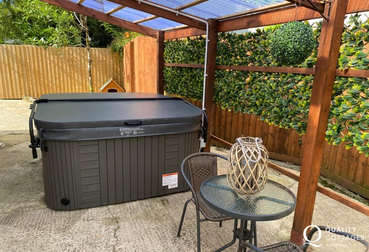 Enclosed patio garden with seating, fire pit and luxury hot tub under canopy - holiday cottage near Amroth, Pembrokeshire.