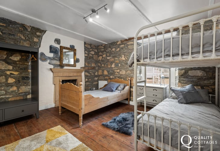 Children's bedroom with bunk bed and single bed in coastal holiday cottage in Newport, Pembrokeshire. Sleeps 10 people.