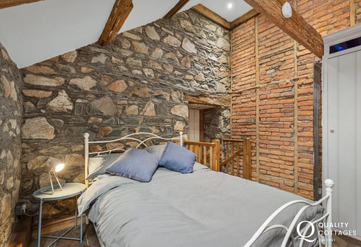 Double bedroom with exposed stone walls and roll top bath in holiday cottage in Newport, Pembrokeshire.