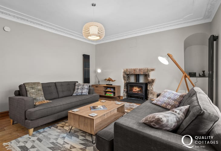 Lounge of dog friendly large holiday cottage in Newport, Pembrokeshire with sofas and log burner.