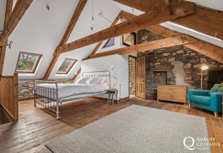 Large attic bedroom with ensuite, exposed stone walls and beams in characterful holiday cottage in Newport, Pembrokeshire.
