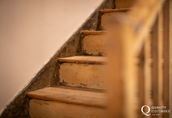 Exposed wood staircase in large traditional exposed stone holiday cottage in Newport, Pembrokeshire.