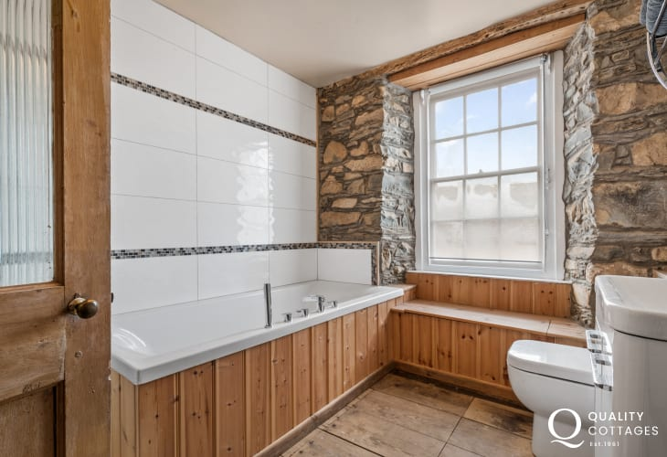 Family bathroom with WC, bath, shower and wash basin in coastal holiday cottage in Newport, Pembrokeshire. Sleeps 10 people.