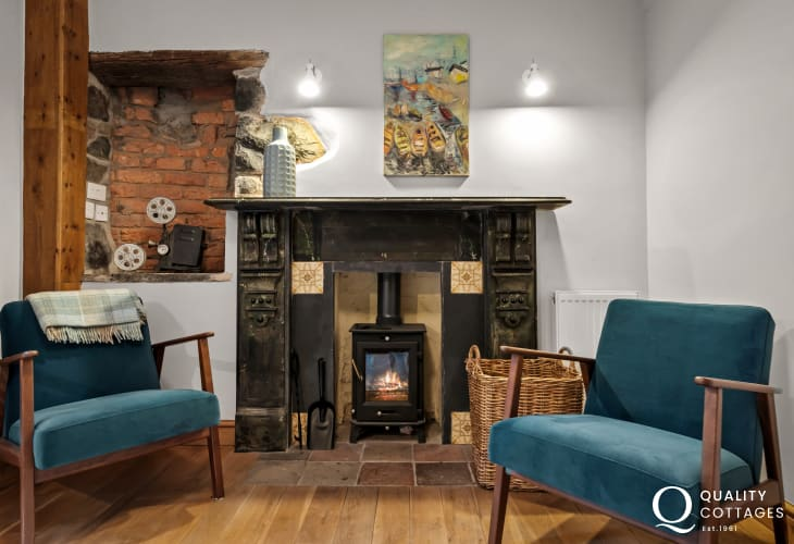 Snug lounge with chairs and wood burner inside holiday cottage in Newport, Pembrokeshire.