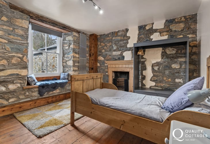 Children's bedroom with stone walls, bunk bed and single sleigh bed in holiday cottage in Newport, Pembrokeshire.